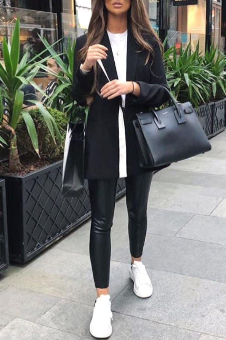 Mode lässig schicke Frau mit Kunstleder-Leggings, schwarzem Blazer und Turnschu