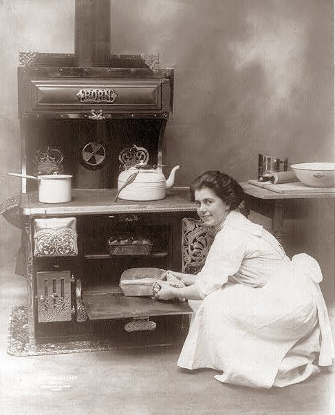 1909 - woman cooking in an old wood stove.