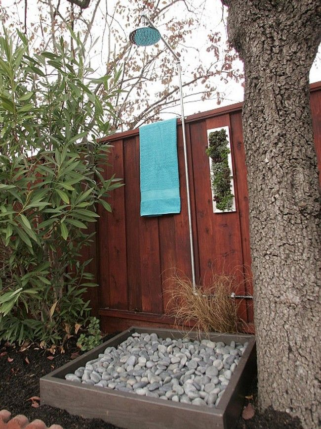 Small, outdoor shower area with floor made from pebbles