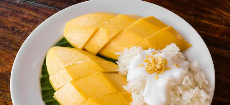 Rijpe, zoete mango met gestoomde sticky rice, kokossaus met een klein tikje zout en knapperig gefrituurde mungbonen, dit dessert is een klassieker uit Thailand.