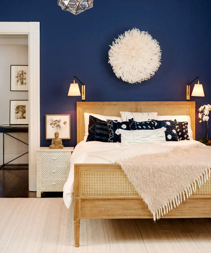 Navy bedroom with juju hat as art above bed