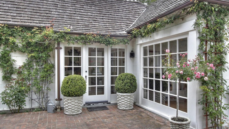 Love these patio doors and the garden urns with the balls and the rose tree.