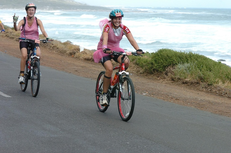 A female cyclist rides with a pink dress over her cycling outfit