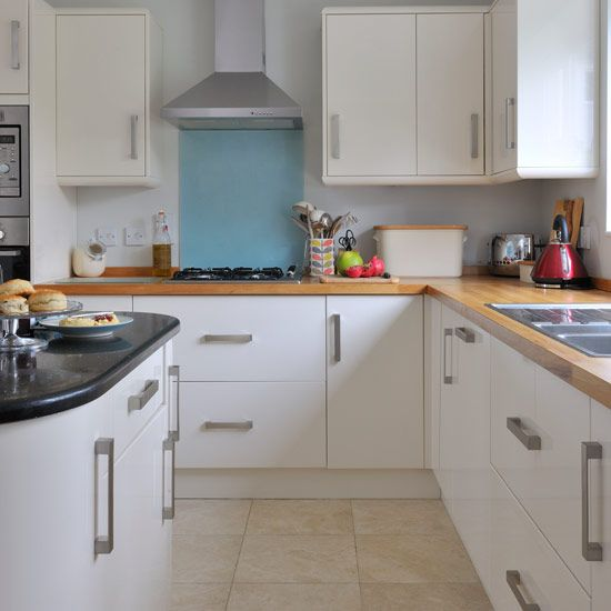 White fitted kitchen with wooden worktop and light blue ceramic tiles above cooker and tiled flooring.