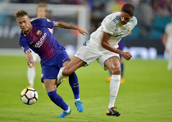 Neymar (L) of Barcelona vies for the ball with Raphael Varane (R) of Real Madrid during their International Champions Cup football match at Hard Rock Stadium on July 29, 2017 in Miami, Florida.      / AFP PHOTO / HECTOR RETAMAL / The erroneous mention[s] appearing in the metadata of this photo by HECTOR RETAMAL has been modified in AFP systems in the following manner: [Raphael Varane] instead of [Nacho]. Please immediately remove the erroneous mention[s] from all your online services and…