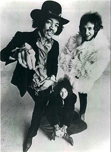 HENDRIX  A black and white photograph of three men, one is sitting on the floor.