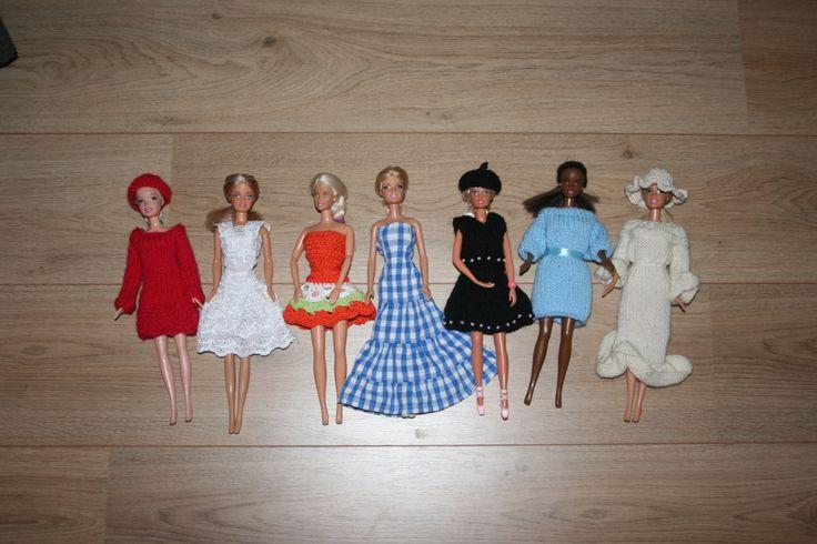 """Voor de barbie's, van links naar rechts: Gebreid jurkje met gebreide muts, jurkje van restje kant, gehaakt jurkje, jurkje van restje van oude herenblouse, gebreid pakje met kraaltjes en gehaakt pinopetje, gebreide jurk, gebreide jurk met gehaakte hoed. """"Uit de losse pols"""" alleen de witte jurk is van een patroon."""