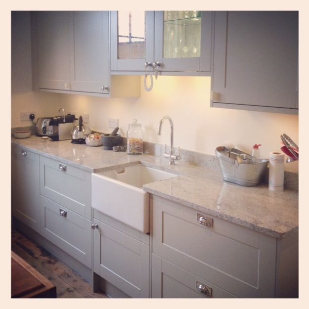 Painted light grey wood kitchen with marble worktops and wood floor