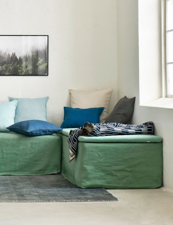 a daybed serves double duty as both a sofa and bed | Bemz offers a range of daybed covers in all of our 250+ colours | modern industrial loft living | green daybed with blue and yellow cushion covers | Bemz daybed cover in Thyme Designers Guild linen