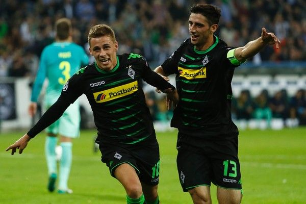 Moenchengladbach's Belgian midfielder Thorgan Hazard (L) celebrates after scoring the opening goal with Moenchengladbach's forward Lars Stindl during the UEFA Champions League first-leg group C football match between Borussia Moenchengladbach and FC Barcelona at the Borussia Park in Moenchengladbach, western Germany on September 28, 2016. / AFP / Odd ANDERSEN