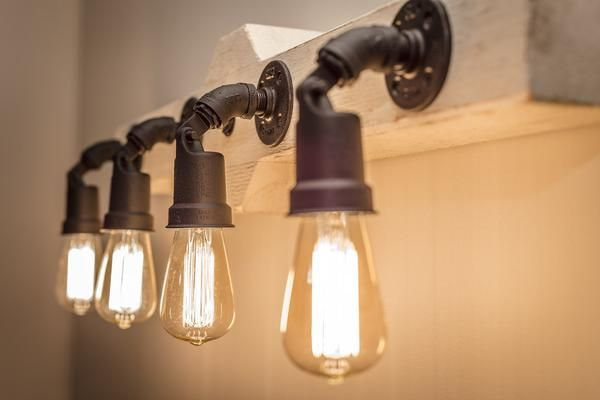 """Reclaimed 4"""" wood beams are wired wired with 6 Edison style light bulbs, then hung with hand forged iron hardware and heavy duty chains."""