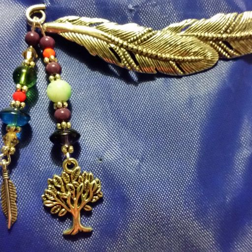 an unusual pin of two large feathers, with a dangle with a tree.  how cool is that?