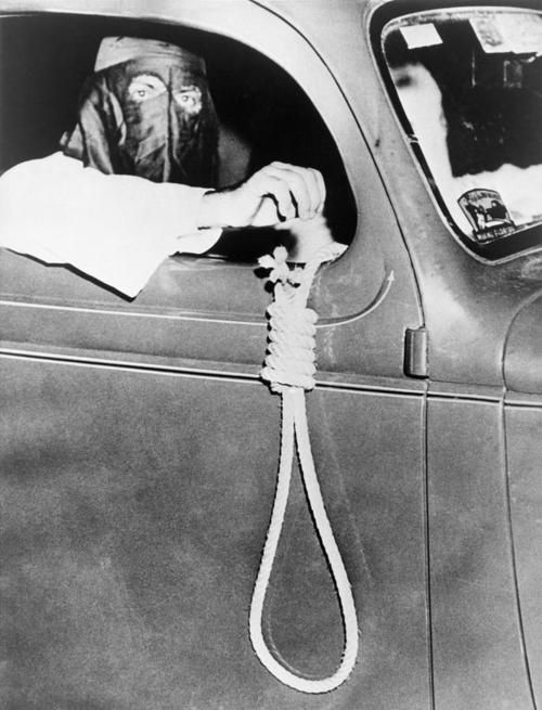 May 1939 - Masked Ku Klux Klan member holds a noose outside a car window during a parade through an African American neighborhood of Miami on the night before a primary election.