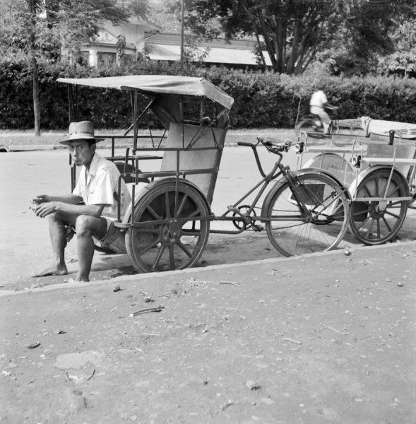 Een riksja-chauffeur wacht langs de straat bij zijn fietstaxi op klanten, Indonesië (1947)