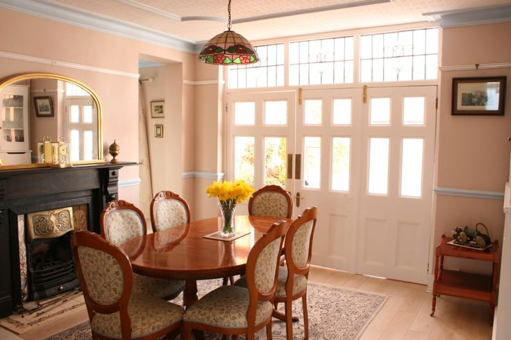 Dining Room with feature slate fireplace, decorative coving, radiator cover with cupboard over archway to study. Wooden doors to access conservatory and lower ground floor garden flat.