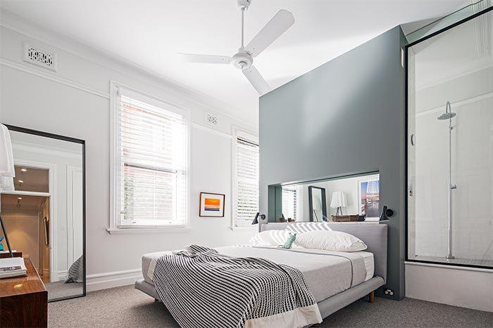 Cada día veo más dormitorios que integran el baño colocando un tabique pegado alcabecero de cama, que bien llega hasta el techo, como aquí, o que llega amedia altura y tras el que se ubica o más bien se escondela zona de aseo, sin puertas, ni cortinas ni separaciones de ningún tipo. En este caso …
