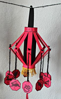 Chinese New Year Lanterns: I really like how the zodiac animals are dangling from the lantern and the top rim features calligraphy!