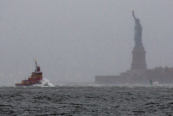 Waves crash over the bow of a tug boat as it passes near the Statue of Liberty in New York (AP Photo/Craig Ruttle).