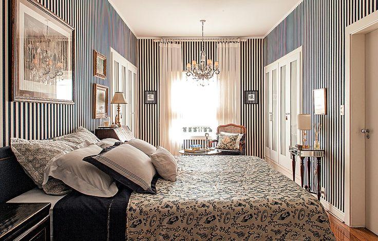 O arquiteto Rogério Ribas respeitou a linguagem da casa, dos anos 1940. Vetada a reforma, a solução para dar mais graça ao quarto foi revestir as paredes com lona listrada azul-marinho. A roupa de cama segue o tom, mas com estampa diferente