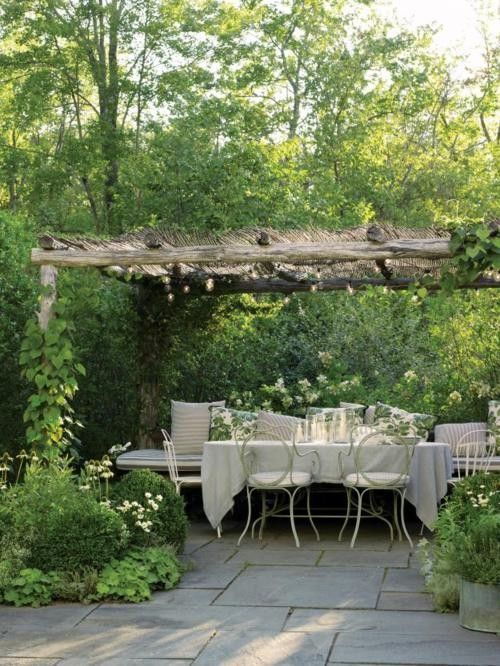 Beautiful pergola and sitting area, surrounded lush lush green gardens and a stone slab patio.