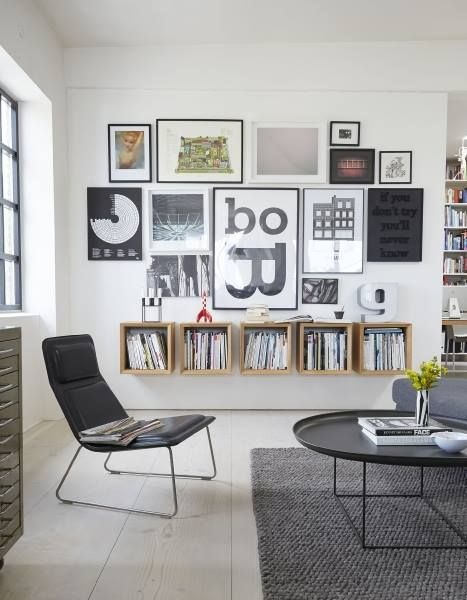 Nice liv ing room with minimal furniture and an art wall above these cubic boxes which have been used in place of a bookcase| @andwhatelse