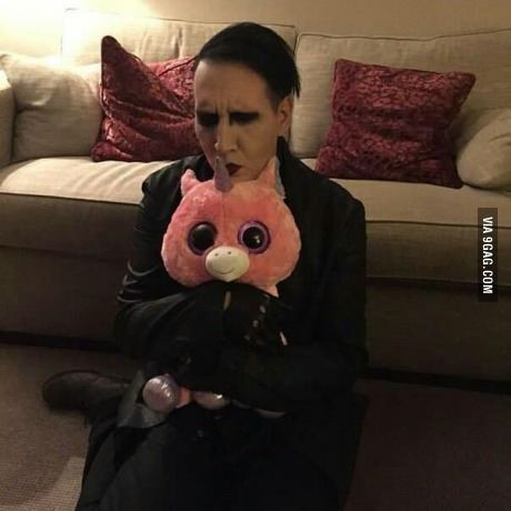 Just Marilyn Manson holding a pink fluffy plush unicorn.