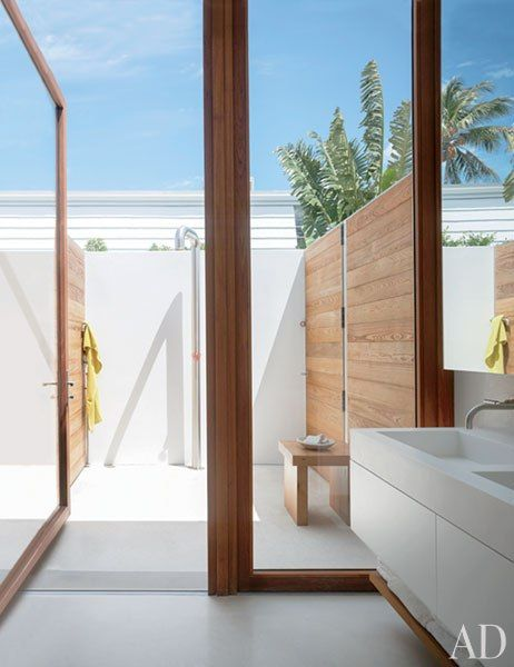 In the master bath, the double sink is of Corian; the teak-framed glass doors lead to an outdoor shower.                                                                                                                                                     More