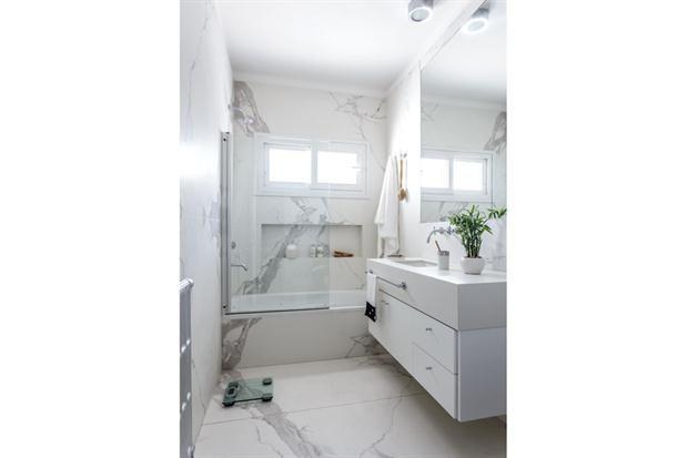 Un baño reciclado para ganar luz y amplitud  Las arquitectas de Estudio Arce eligieron un cerramiento más moderno para la ventana, y se creó un nicho con luces dicroicas embutidas en la pared de la ducha. El vanitory se reemplazó por un mueble colgante a medida con mesada de Neolith.  /Daniel Karp