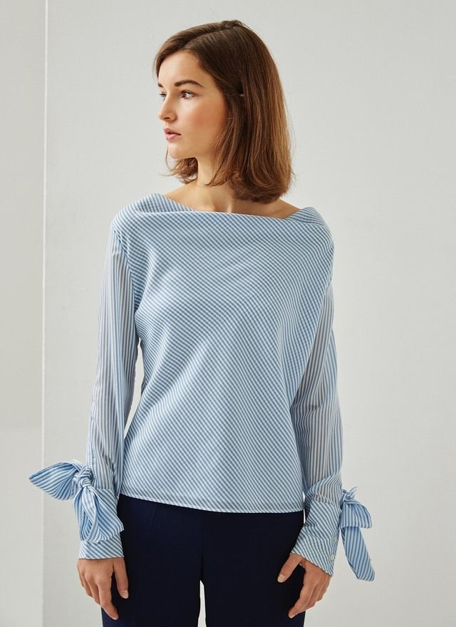Blusa de rayas en mezcla de poliester y liocel con un sofisticado escote cascada. Corte recto y manga larga con ojal de botones y lazada extraíble.
