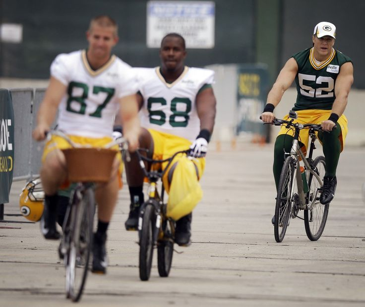 Clay Matthews (52) rides a bike with teammates Jordy Nelson (87) and Kevin Hughes (68) to NFL football training camp Friday, July 26, 2013