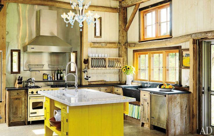 In a 200-year-old barn that she transported to coastal Rhode Island, designer Ellen Denisevich-Grickis created an eclectic kitchen setting: Rustic beams mix with a vibrant Shaker-style island, Murano-glass chandelier, and Viking stainless-steel appliances. The concrete floors are embedded with chips of mirror, mother-of-pearl, abalone shell, and sea glass.