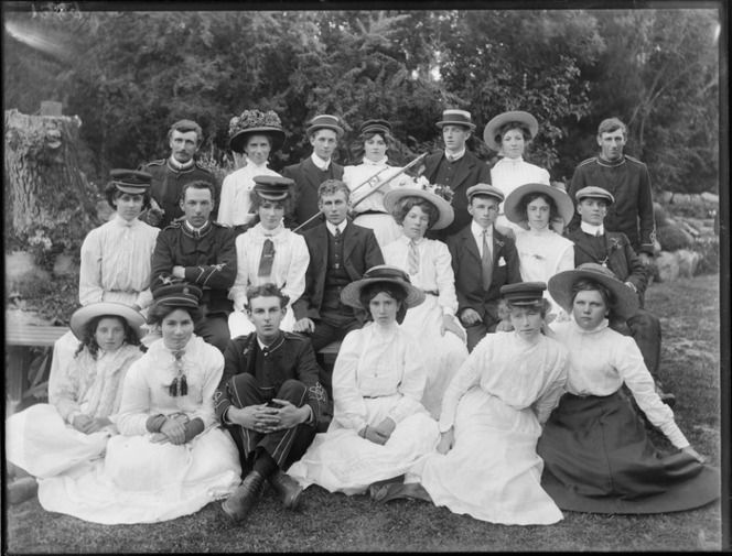 A group of unidentified people, men and women, showing some of the men wearing a brass band uniform, a women in the back row holding a slide trombone, in an unidentified park, possibly Christchurch district