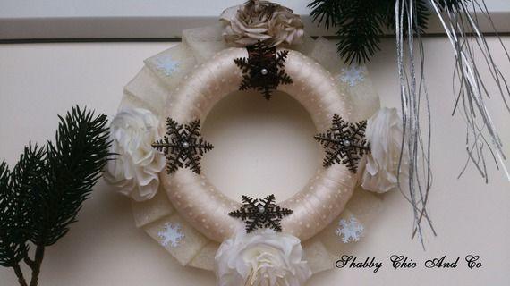 Superbe couronne de l'Avent simple et chic à la fois. Faite artisanalement. Le cercle de la couronne, symbolisant l'éternité, est recouvert avec 4 m de ruban de soie couleur ivoire à poids blancs. Les 4 fleurs, symbolisant les points cardinaux, sont faites en papier de filtre à café. Celle du haut est teintée par mes soins. Un flocon en métal, façon bronze, accompagne chaque rose et ont une perle en leur centre. Le tout est terminé par un frou-frou de tulle écru avec des petits flocons…