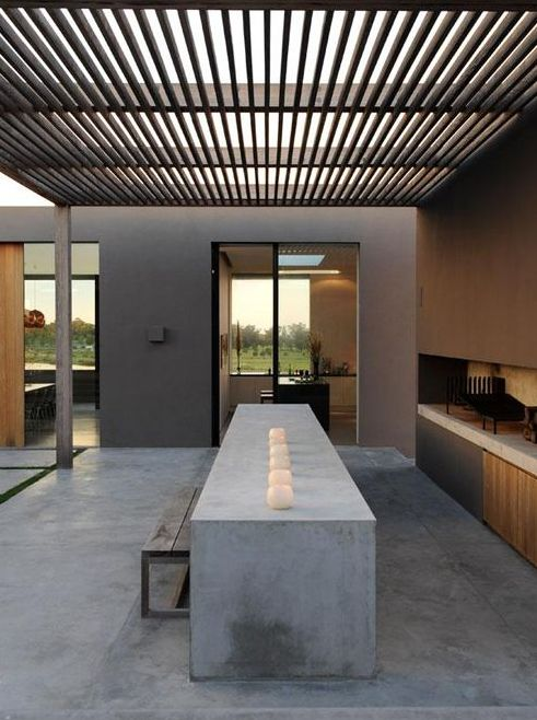 Covered area with long concrete kitchen bench and sleek BBQ station