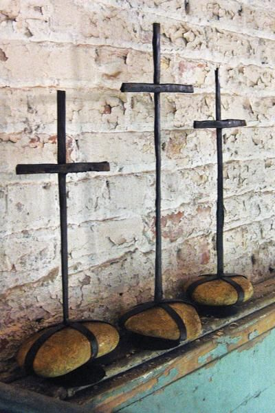 Set of three scrap iron crosses with caged rock bases. Cool yard art