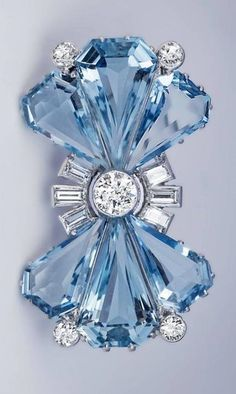 An Art Deco platinum, aquamarine and diamond bow brooch, circa 1935. The brooch is marked with platinum and maker's marks. #luxuryjewelry #gemstonebrooches