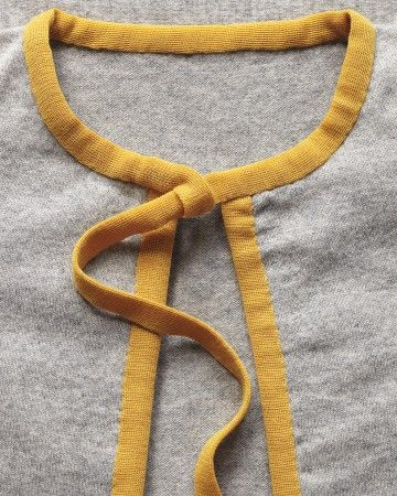 Color-block in small doses. Remove buttons. Cut precreased tape to fit both sides of placket and around collar. Stitch in place; bind placket first, covering buttonholes. Optional: Create a loop at 1 side of collar, and leave a tail at other side to thread through. Wool knit binder tape (#2004), 30 mm, in color #22, $5.25 per yd., from Shindo, 212-868-9311.