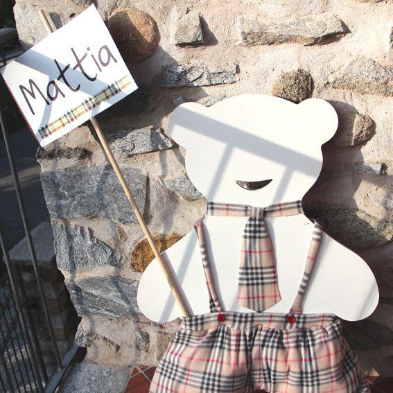 sagoma orsetto con pantaloncini e cravatta burberry, posto come benvenuto all'ingresso della sala ricevimento battesimo