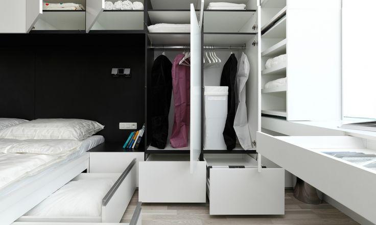 Úložné priestory v spálni apartmánu sme navrhli tak, aby nezaberali viac plochy, ako je nevyhnutné. V spodných častiach nábytku vrátane postele sme navrhli výsuvy, ktoré považujeme z hľadiska prístupu za najkomfortnejšie. Výsuvný šuflík nad stolom je netypickým riešením, pretože jeho obsah je prístupný zboku, nie zhora.