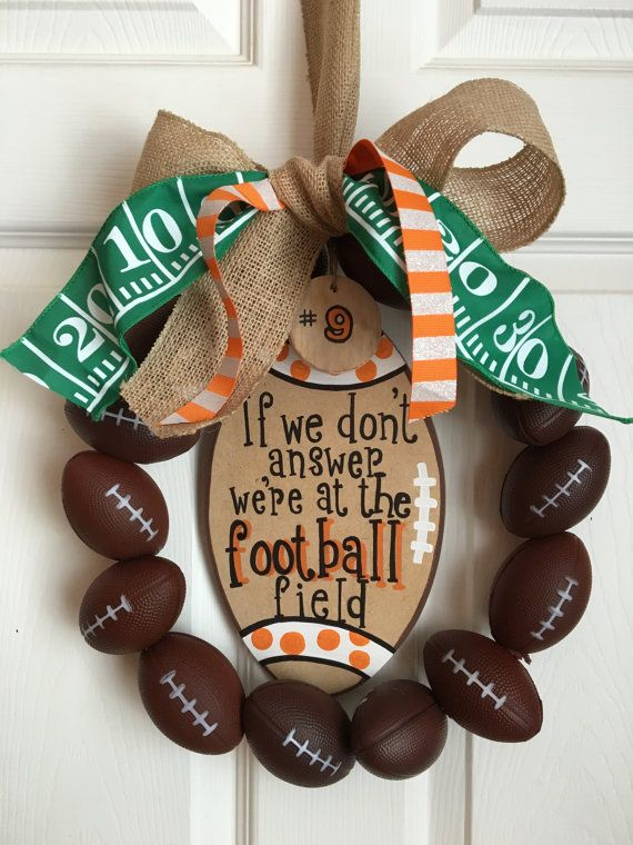The perfect wreath for a football family! This wreath with 14 brown foam footballs, a personalized hand-painted sign, a burlap bow, decorative football yard line ribbon, and orange/white striped accent ribbon. The standard sign will have orange dots painted on the ends of the football. The sign will read, If we dont answer were at the football field, but can be customized to say anything youd like (players name, number, team name). A wooden circle can be added to display a number or logo for…