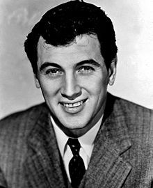 Rock Hudson (born Roy Harold Scherer, Jr., November 17, 1925– October 2, 1985), was an American film and television actor. Widely known as a leading man in the 50s and 60s (often starring in romantic comedies opposite Doris Day), Hudson is also recognized for dramatic roles. . He completed  70 motion pictures and starred in several television productions during a career that spanned over four decades.  Hudson died in 1985 and was the first major celebrity to die from an AIDS-related illness