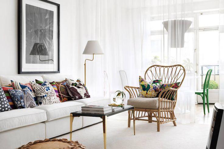 Wiklinowy fotel i wzorzyste poduszki na białej kanapie wprowadzają do tego salonu kolonialny klimat. Z klasyczną lampą i eleganckim stolikiem na mosiężnych nogach kontrastuje nowoczesna czarno-biała fotografia w ramie. Zwiewnymi półprzejrzystymi zasłonami dyskretnie oddzielono aneks wypoczynkowy od jadalni.