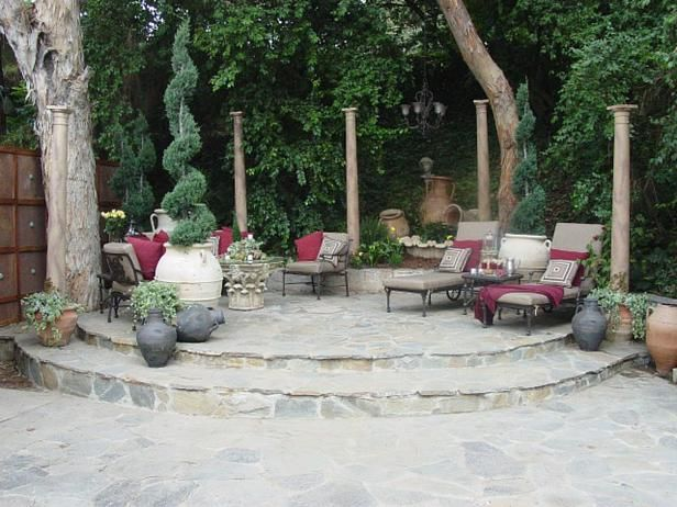 After: The fountain sections are repurposed into a smaller tiered water feature and the pediments are used as side tables. Painted wooden columns staked into the ground and cemented into pots add Old World charm, height and definition to the patio area. furniture (all from the Elise line): single chaise lounge 1007-9, coffee table 1031-f-Elise, square end table 1031-e-Elise, triple club 1007-23, single club 1007-21) (Caluco Quality Patio Furniture) wooden columns (Lowe's)