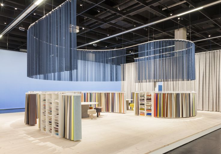 Our stand at Orgatec is organised in a subtle, flowy S-shape. The curved curtain rail overhead is mirrored in the looped row of airy, coloured slivers of textiles on the floor.  Photo: Patricia Parinejad