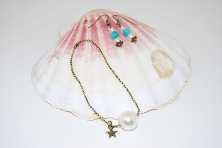 Pendientes Amazonitas: Los pendientes son largos y están formados por piedras semipreciosas amazonitas azules y perlas de cristal blanco. Su terminación son casquillas color bronce con forma de flor.