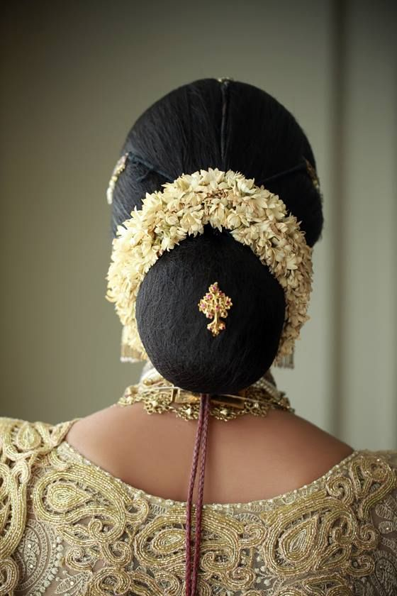 What a beautiful large low bun with real flower gajra & judapin! Care however should be taken before adopting such hairstyles, as due to it's high static charge, it will cause phlegm to move up in the throat, causing the voice to quaver & a frequent urge to clear the throat. A heavy chabi chhalla with a long & wide hook if inserted at the edge of the pleats of the saree, will reduce this problem as it's hook will activate the acupressure points that act to keep the throat clear.