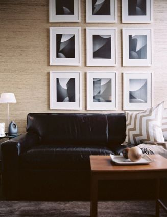 living rooms - sand beige grasscloth wallpaper chocolate brown rug black leather sofa white gallery frames art taupe zigzag chevron silk pillows
