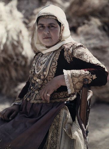 A woman wears the costume of Megara worn for Easter Tuesday dance. National Geographic's Greece in Color from the 1920s Photographer: Maynard Owen Williams in the 1920s.