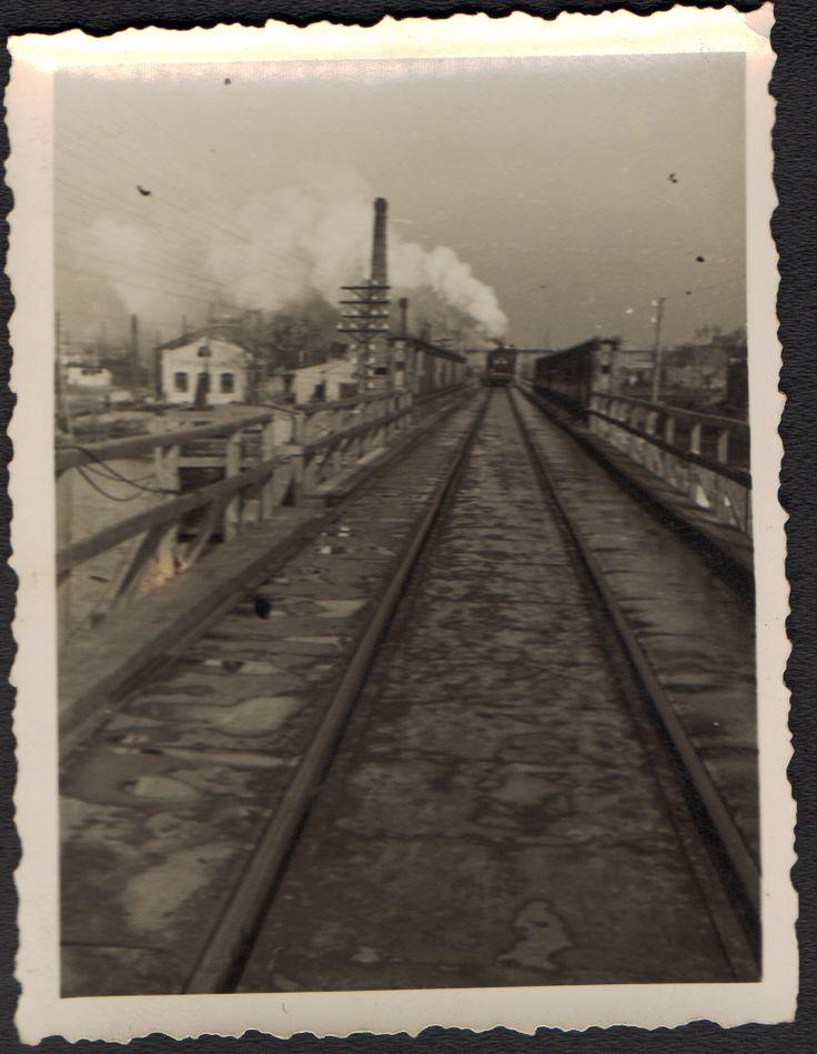 """Вид с юга на север на железнодорожное полотно пути, ведущего к """"Литерному"""" железнодорожному мосту. Этот мост за спиной фотографа. Впереди, чуть левее в кадре видна труба теплоэлектростанции. Повыше приближающегося со стороны вокзала поезда, видна """"поперечина"""" недостроенного до войны """"Стачкиного"""" моста. Справа в кадре, за ограждением насыпи, видно понижение. Это русло реки Темерник. (Идентификация В.В. Долбнина)"""