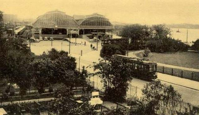 station Rotterdam Maas stationsgebouw I (1930) bedoeld als voorlopig gebouw. uit hout gebouwd. Rotterdam Maas in de dertiger jaren. De gloednieuwe vierassige motorwagen van de R.E.T heeft zojuist het station verlaten en is op weg naar de stad. Deze Motorwagen komt uit de Alanfabriek die eerst aan de Oudedijk 149 gevestig was en daar na aan de Kleiweg waar nu de Remise van de RET is gevestigd